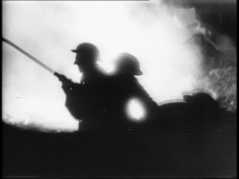 shots of flames burn in the night while fire fighters try to extinguish the blazes / shots of smoke hanging low over london streets / shots of help... - anno 1944 video stock e b–roll