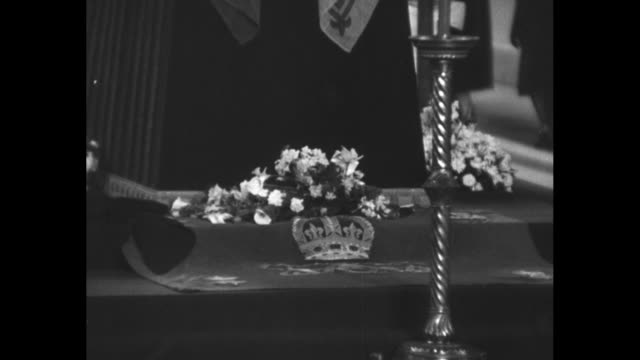 vídeos de stock, filmes e b-roll de cu shots of king george vi's draped coffin lying in state in westminster hall topped with crown and wreath cross beside it and candles lit / mourners... - 1952