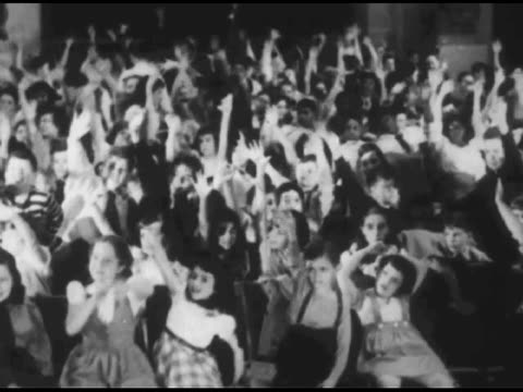 vídeos y material grabado en eventos de stock de / shots of large audience people walking / various people on stage eventually act out a musical noisemaking routine children watch a performance on... - 1951