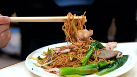 2 shots of man eating tossed noodle with pork and boiled pork liver - noodles stock videos & royalty-free footage