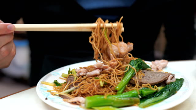 2 Shots of man eating Tossed Noodle with Pork and Boiled Pork Liver