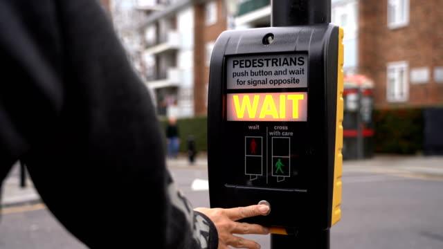 vídeos y material grabado en eventos de stock de 2 disparos de hombre botón de semáforo en camino de intersección, londres, reino unido - luz verde semáforo