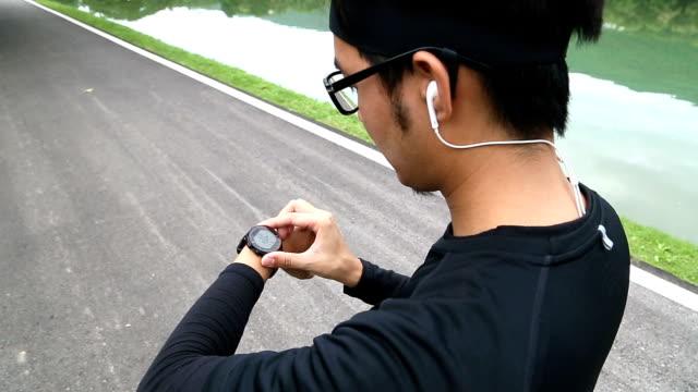 vídeos de stock, filmes e b-roll de 2 tiros de homem usando frequência cardíaca monitor relógio para correr - óculos