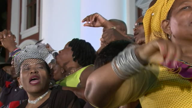 Shots of people celebrating around the bust of Nelson Mandela following Cyril Ramaphosa's first state of the nation address in Cape Town South Africa