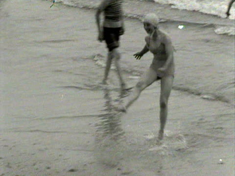 Shots of people paddling and swimming on Bournemouth beach 1954