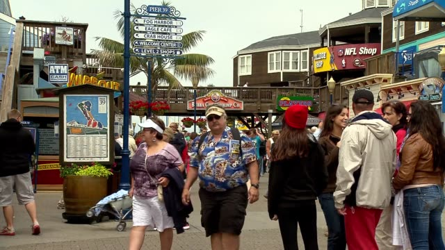 stockvideo's en b-roll-footage met shots of pier 39 in san francisco on july 17 a wide shot of flags waving at pier 39 with tourists passing by shops a wide shot of tourists walking... - pier 39