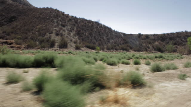 pov shots of plants and mountains while driving along desert road / santa clarita, california, united states - santa clarita bildbanksvideor och videomaterial från bakom kulisserna