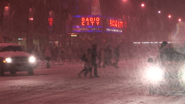 shots of radio city music hall with pedestrians and tourists out and about at the height of the storm available in hd - radio city music hall stock videos & royalty-free footage