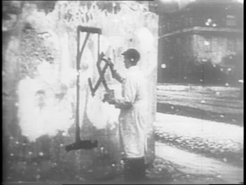 Shots of resistance fighters painting on public walls with the word Verloren which means forsaken / Shots of painted slogans converting swastikas to...