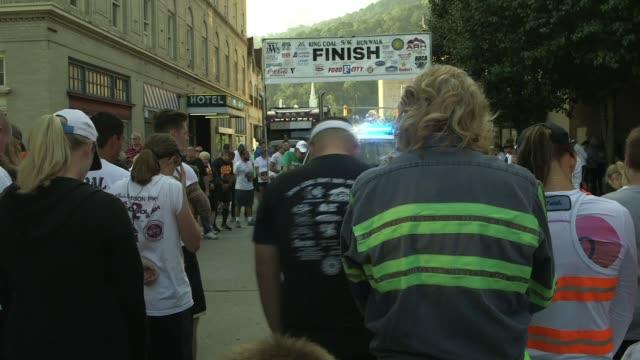 shots of runners in downtown williamson west virginia - ランニングショートパンツ点の映像素材/bロール