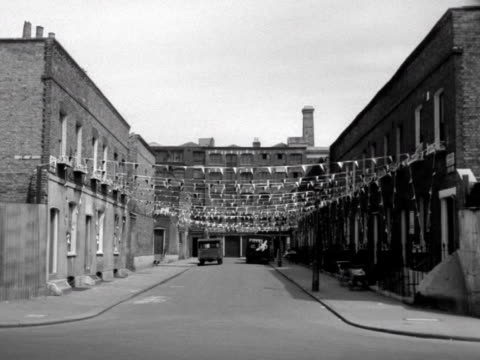 Shots of terraced streets decorated with bunting and flags in preparation for the coronation of Elizabeth II 1953