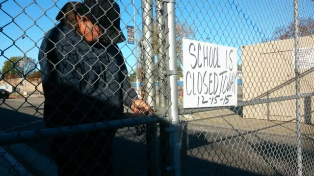 """shots of the closed mulholland middle school. clip 1 is a school administrator locking the school entrance gate with sign that reads """"school is... - gate stock videos & royalty-free footage"""
