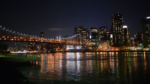 Shots of the Queensboro Bridge and the Manhattan New York skyline lit up at night from the Queens side of the East River Shots of cars driving up the...