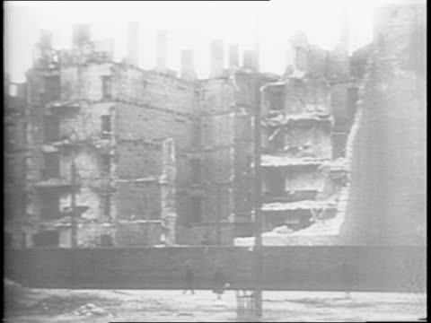 shots of the rubble and ruins inside warsaw ghetto / tilt down shot of nazi poster listing poles killed at lublin / shot of member of polish... - 1944 bildbanksvideor och videomaterial från bakom kulisserna