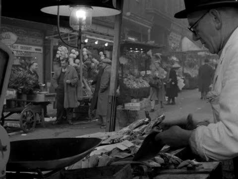 stockvideo's en b-roll-footage met shots of the various stalls at berwick street market soho customers browse and purchase fruit vegetables gloves fabrics stockings and jewellery 1954 - panty