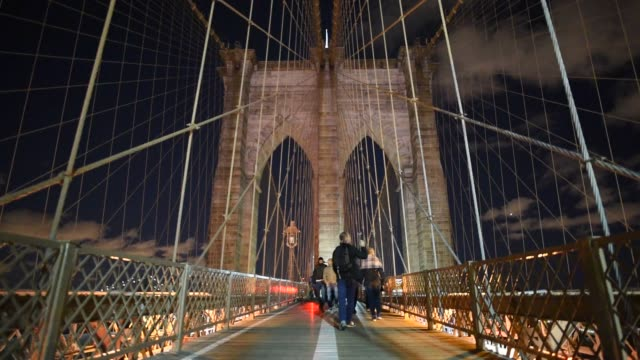 Shots of tourists and commuters walking down the walking path across the Brooklyn Bridge with the support structures lit up at night above them in...