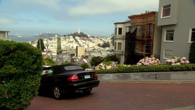 shots of tourists overlooking lombard street in san francisco on july 17 a medium shot of tourists overlooking lombard street and the coit tower,... - coit tower stock videos & royalty-free footage