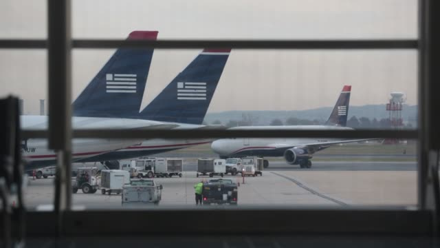stockvideo's en b-roll-footage met shots of us airways airplanes from inside an airport terminal at ronald reagan national airport in washington dc passengers carrying luggage walk... - us airways