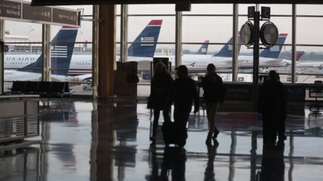 vidéos et rushes de shots of us airways airplanes from inside an airport terminal at ronald reagan national airport in washington dc passengers carrying luggage walk... - aéroport ronald reagan