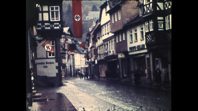 shots of various buildings on the street covered in nazi swastika flags; people walking in the street and close up of a no parking sign - no parking sign stock videos & royalty-free footage