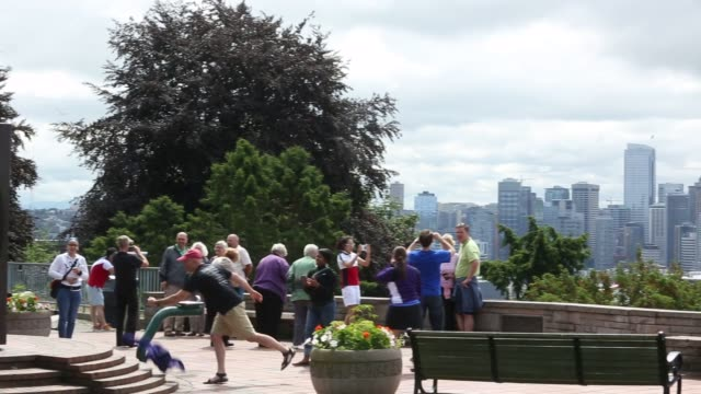 vídeos de stock e filmes b-roll de shots of visitors and tourists visiting kerry park in seattle washington children play in a sculpture playground as their parents watch them from a... - space needle