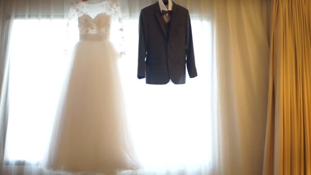 3 shots of wedding dress and suit hanging in front of window. - wedding dress stock videos and b-roll footage