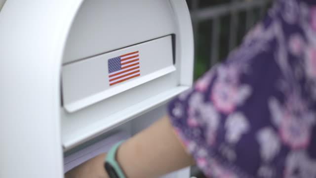 不在者投票を自宅の前の郵便受けに入れる女性の2ショット。 - 米国大統領選挙点の映像素材/bロール