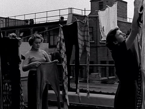 shots of women hanging out ballet tights on a washing line on the roof of the royal opera house before panning down onto the street below where... - collant video stock e b–roll