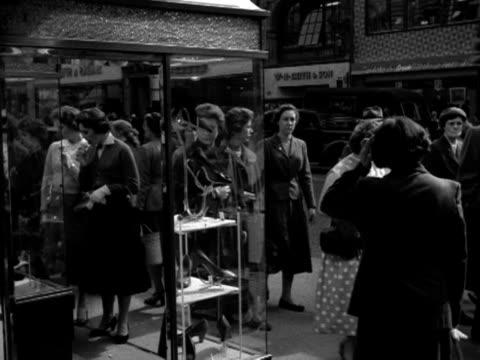 shots of women window shopping in london. 1956. - ウェストエンド点の映像素材/bロール