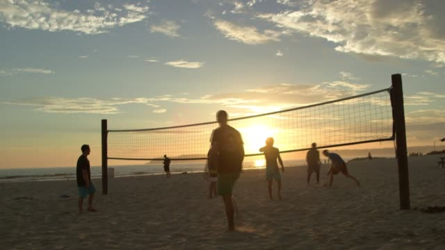 shots of young men and women playing volleyball on the beach of san diego california with the sun setting in the background a group of crossfit... - volleyball sport stock videos & royalty-free footage