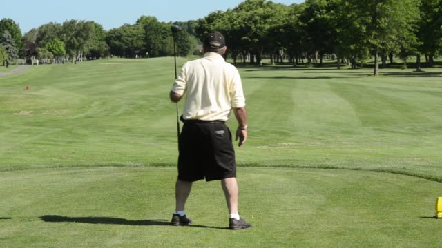 Shots pan across a golf green at Cherry Creek golf course in Riverhead Long Island New York A middle age man stands at a golf tee and sets up for a...