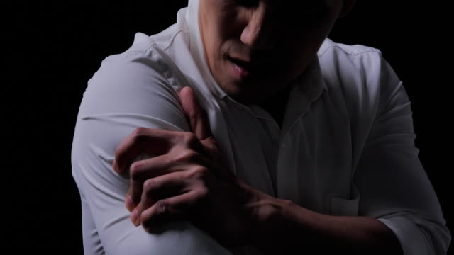 shoulder injuries, young man with pain in shoulder, ache in human body on black background.office syndrome, lifestyles, health care, medical, people concept.sick at home - body concern stock videos & royalty-free footage