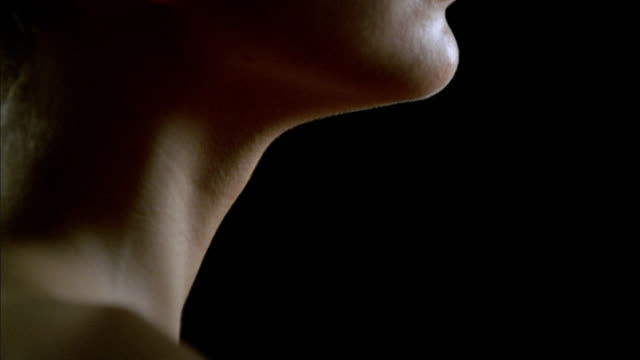cu pan shoulders, lower face, and neck of woman and man facing each other against black background/ new york, new york - 肩点の映像素材/bロール