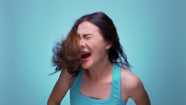 Shouting woman on isolated blue background slow motion