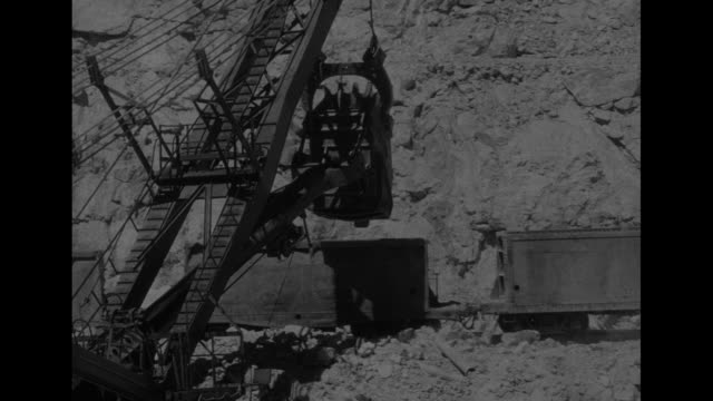 VS shovel digs up dirt and deposits it in train cars / VS hand points to rocks in ground and copper in rocks / VS crane moves segment of track into...