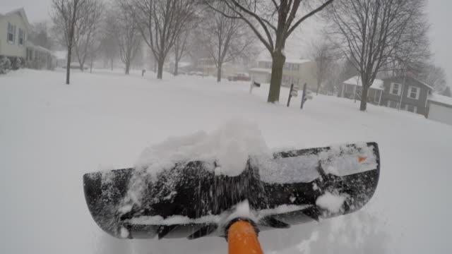 vídeos de stock e filmes b-roll de shovel snow after winter storm point of view pov - pá para neve