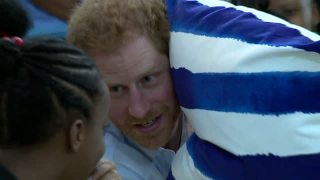 Show interior shots Prince Harry chatting with two girls and hiding behind cushion to whisper at The Nightengale Children's Home Prince Harry is...