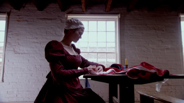 MS POV Show of Reenactment Mary Pickersgill as she sits next to a window sewing the Star Spangled Banner / Baltimore, Maryland, United States