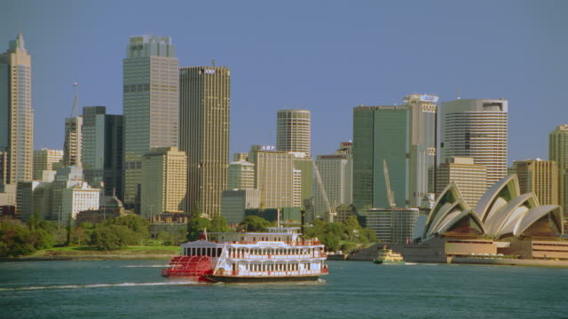 "PAN ""Showboat II"" riverbaot moving through harbor near skyline + Opera House / Sydney, Australia"