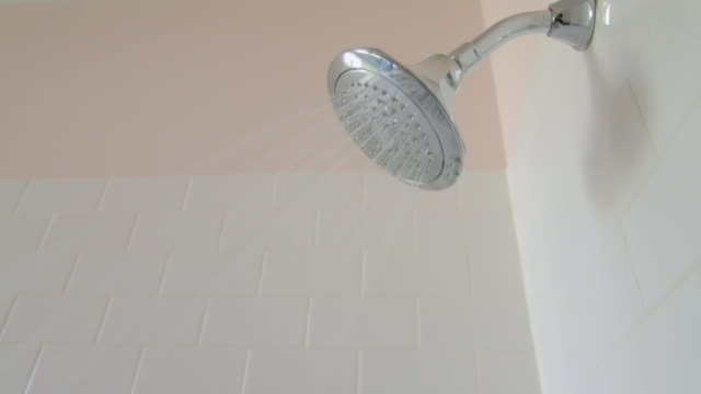 shower head with water spraying out of it - duschkopf stock-videos und b-roll-filmmaterial