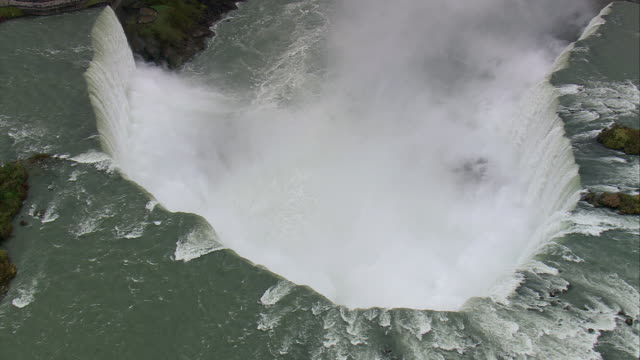 vídeos de stock, filmes e b-roll de aerial showering spray from the falling water of niagara's horseshoe falls / niagara falls, new york, united states - niagara falls