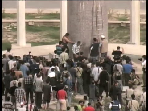 vídeos de stock e filmes b-roll de sequence showing saddam hussein statue being attacked and statue being pulled from plinth and dragged along ground in firdos square statue of saddam... - estátua