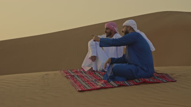 showing the place to his colleague in the desert - eid mubarak stock videos & royalty-free footage