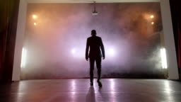 Showman. Young male entertainer, presenter or actor on stage. Back, arms to sides, smoke on background of spotlight.