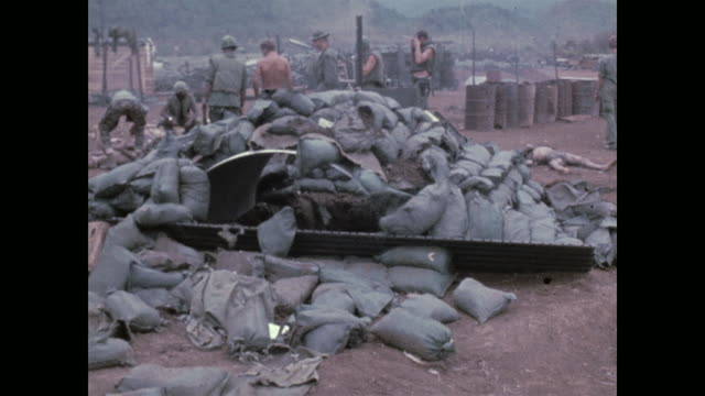 shows a bunker blown up when a north vietnamese commando threw an explosive charge inside during a nighttime attack / shows hat and boot of the... - vietnamkrieg stock-videos und b-roll-filmmaterial