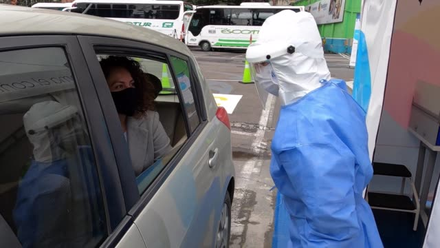 shows a covid-19 drive-thru test point on may 13, 2020 in bogota. the drive-thru test point, the first in colombia, had a capacity to take 1,400... - getting dressed stock videos & royalty-free footage