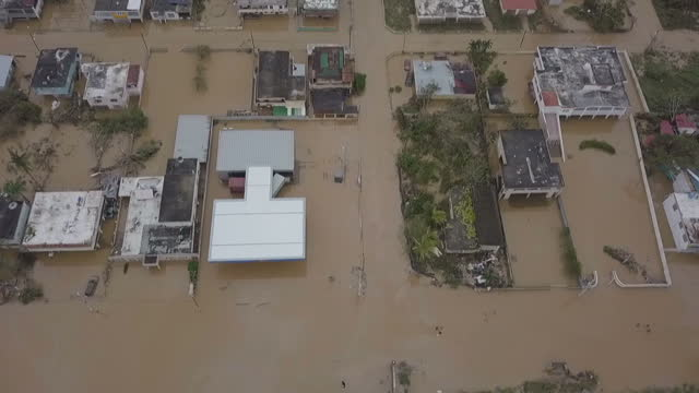 Shows aerial drone shots birds eye shots flying over flooded residential neighbourhood in Toa Baha 15 people are known to have died and 20 more are...