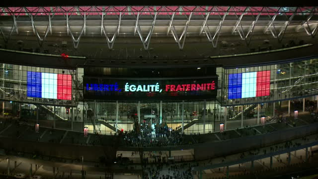 Shows Aerial night shots Wembley Stadium in London lit in red white and blue the colours of the Tricolore French flag Exterior shots fans outside...
