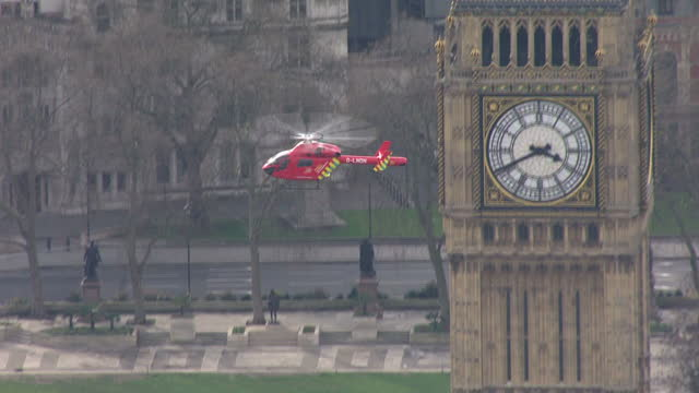 Shows aerial shots air ambulance helicopter taking off from Parliament Square with pan out to show the Houses of Parliament and emergency services on...