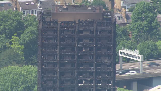 shows aerial shots blackened burnt out remains of grenfell tower block in west london. locals and volunteers have claimed that victims of the... - co ordination stock videos & royalty-free footage